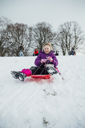 Low angle view of a little girl sledding down a hill in the snow.