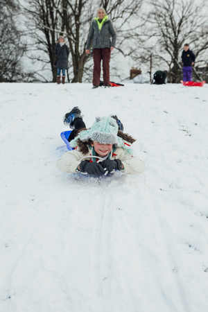 Little girl is lying on her belly on a sled, zooming down a big hill in the snow.