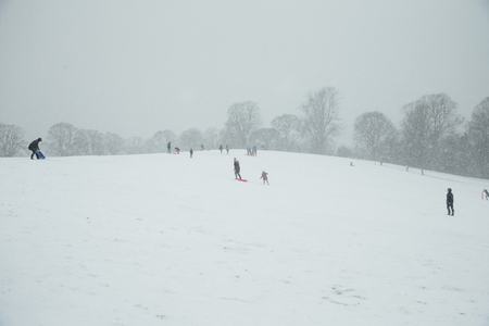 People are outdoors enjoying the snowy weather with sleighs and snow toys.
