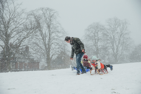 Man is pulling his children along in the snow on sleds.