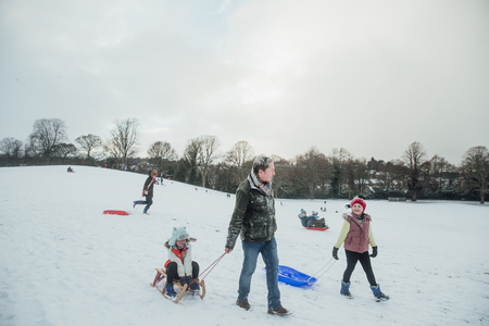 Man is out sledding in the snow with his daughters.