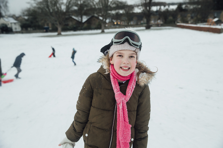 Portrait of a little girl while she is out playing in the snow. Imagens