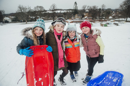 Portrait of a group of friends while out sledding in the snow. Stockfoto