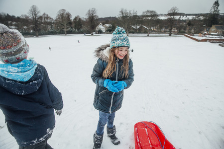 Little girl is having fun in the snow with her friends and family.