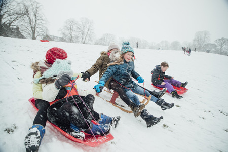 Children are racing each other down a hill on sleds in the snow. The girls are holding hands.