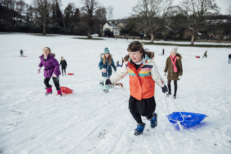 Group of little girls are running up a hill in the snow to have a sled race.