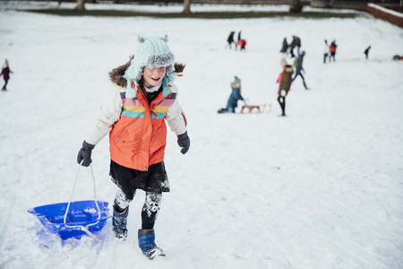 Little girl is walking up a hill, pulling her sled in the snow. Imagens