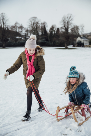 Two little girls are having fun in the snow. One of the girls is pulling the other on a sleigh.