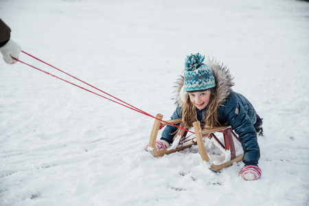 Little girl is smiling for the camera while being pulled on a sleigh in the snow.