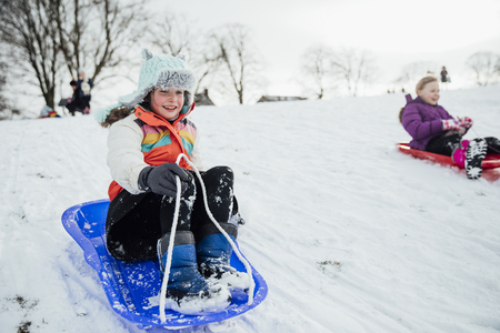 Close up shot of a little girl on a snow sled in a community race.