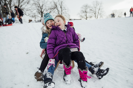 Three little girls are sitting on a sled together, going down a hill in the snow. Imagens