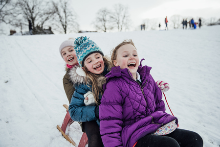 Three little girls are sitting on a sled together, going down a hill in the snow. Stock Photo