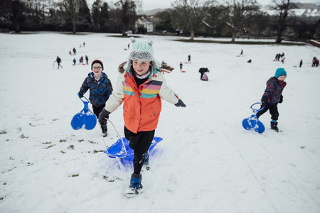 Children from the community are running up a hill to have a race together on sleds in the snow. Imagens