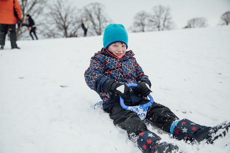 Little boy is smiling for the camera while sliding down  a hill on a sled.