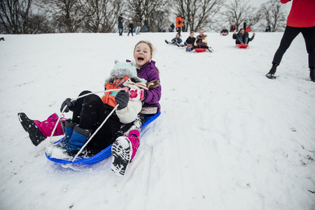 Children from the community are having a sled race in the snow on a big hill in a public park.
