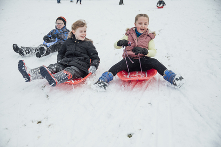 Children from the community are coming down a hill in a  public park on sleds in the snow. Imagens