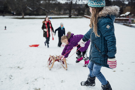 Two little girls are heading up a hill to have a race on a sleigh. One girl is pulling the sled uphill and the other girl is pushing it.