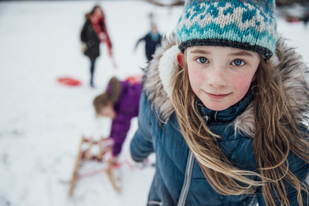 Little girl is looking at the camera while pulling a sled up the hill in the snow with her friends.