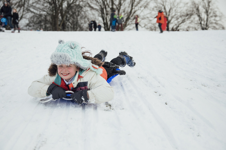 Little girl is lying on her belly on a sled, going down a big snowy hill in a public park.