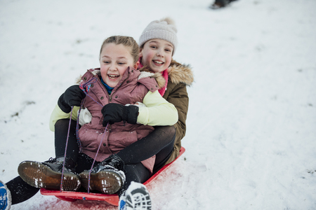 Two little girls are going down a snowy hill together on a sleigh. Imagens