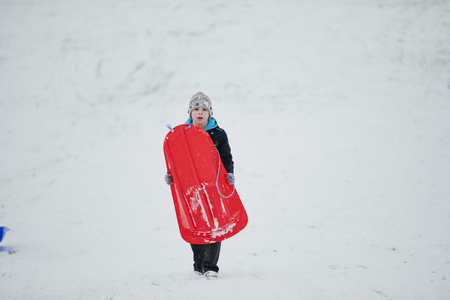 Little boy is walking toward the camera in a public park while it is snowing and is carrying a sled. Stock Photo