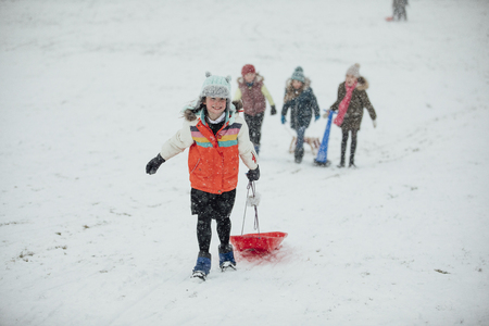 Little girl is running up a hill with her sleigh to have races in the snow. Imagens
