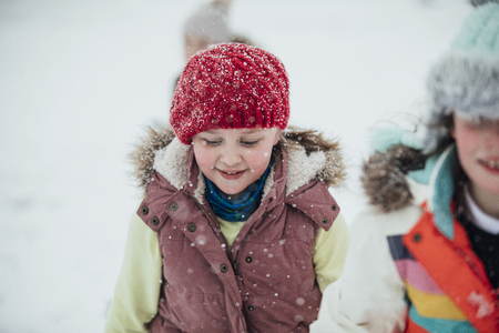 Close up shot of a little girl out in the snow with her friends.