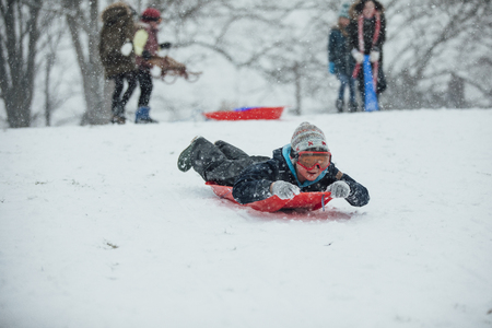 Little boy is lying on a sled, going down a hill in the snow.
