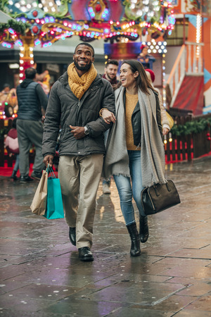 Front view of a happy couple walking along a city street. Behind them is a fun fair ride. The couple are carrying shopping bags. Stock Photo
