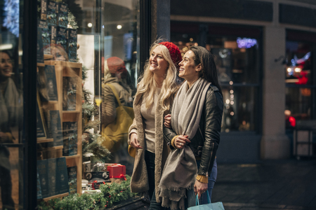 Side view of two mid adult women looking in a store window while doing some christmas shopping. Stock Photo