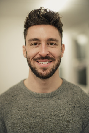 Front view of a young male adult looking and smiling at the camera while he gets a portrait taken. Standard-Bild