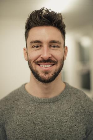 Vorderansicht eines jungen männlichen Erwachsenen, der in die Kamera schaut und lächelt, während er ein Porträt genommen bekommt. Standard-Bild