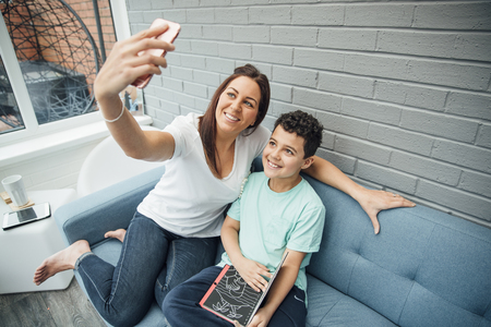Mother and her son are taking a selfie while reading in the conservatory at home.