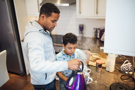 Little boy is helping his father while he makes tea in the morning. Stock Photo