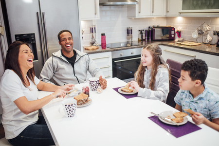 Family of four are enjoying breakfast together at home. They are all laughing while they have toast and jam. Stok Fotoğraf