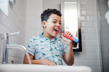 Little boy is brushing his teeth at the bathroom sink in the morning. Foto de archivo