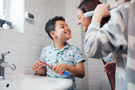 Children are brushing their teeth in the bathroom at home. The mother is checking the little boys mouth to make sure he has brushed properly. 写真素材