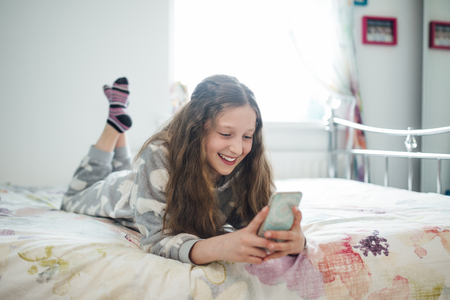 Little girl is lying on her bed, texting on a smart phone.