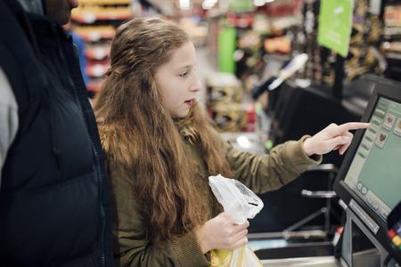 Petite fille est à la caisse en libre-service du supermarché avec son père.