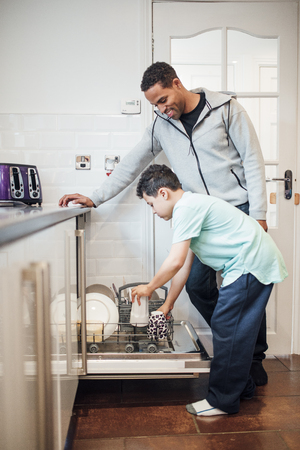 Little boy is helping his father to load the dishwasher at home. 스톡 콘텐츠