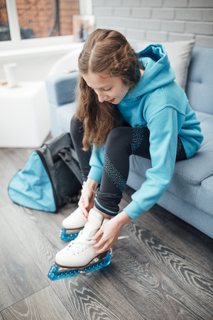 Little girl is putting figure skates on in the conservatory of her home before she goes to her skating lesson.