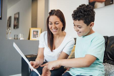 Le petit garçon et sa mère regardent la carte de fête des pères qu'ils ont fabriquée ensemble à la maison.