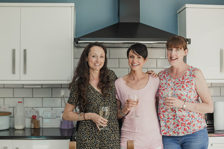 Three mid adult women standing in a kicthen enjoying a glass of wine. The women are all standing around the stove in the kitchen, looking at the camera and smiling. Stock Photo