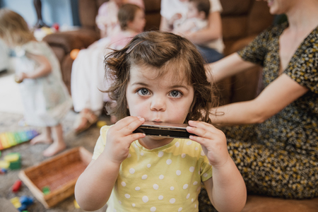 Front view of a little toddler girl looking at the camera. She is having fun and playing the harmonica. In the background ther are other children playing and her mother is sat down next to her. Stock Photo