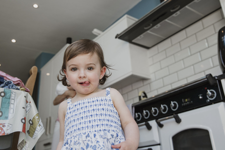 Low nagle view of a little girl looking at the camera. She is stood in the kitchen and pulling a cheeky facial expression with her tongue sticking out. Stock Photo - 107489815