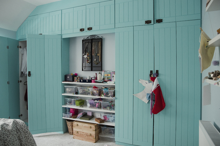 Wide angle view of a bedroom interior with a wardrobe and door partially open. There is also storage space and shelves in the middle between the two built in wardrobes.