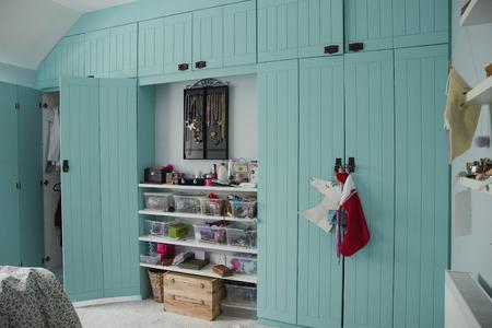 Szeroki kąt widzenia wnętrza sypialni z szafą i częściowo otwartymi drzwiami. Pomiędzy dwiema szafami wnękowymi znajduje się również schowek i półki pośrodku.