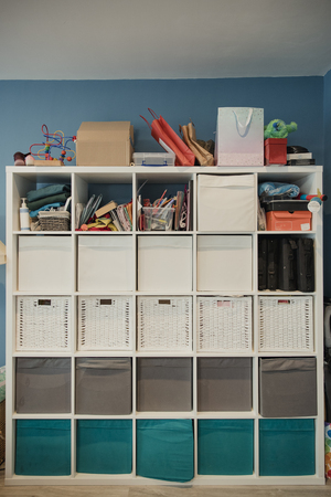 Front view of a storgae unit in a home. The storage unit has many draws and compartments for storage. Some household objects have been stored on top of the unit.
