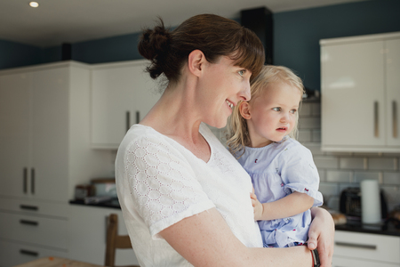 Side view of a mother holding her daughter. They are both looking out the window together while stood in the kitchen at home. Stock Photo