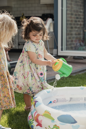 Side view of two little girls standing next to an inflateable pool. One little girl is using a toy watering can to pour water into the pool. Standard-Bild - 107489913